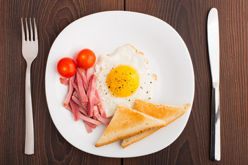 Fried egg with toasts, ham and cherry tomato