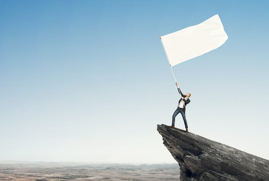 man with blank flag standing on the top of a rock