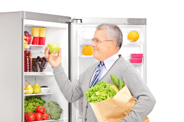 Smiling mature man holding a paper bag near the refrigerator ful