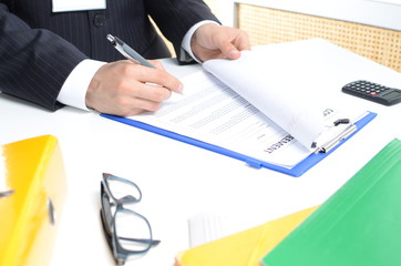 Man in suit signing documents