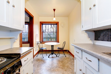 White old kitchen with small dining table.