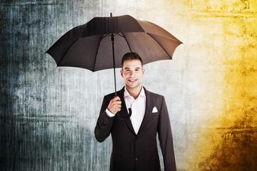 businessman in rain and sun holding umbrella