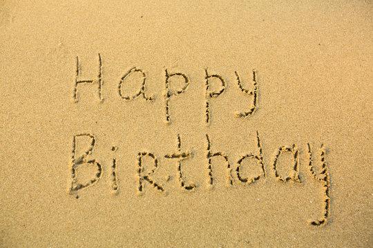 Inscription Happy Birthday on texture of wet sand.