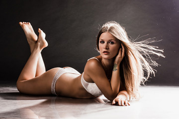 Portrait of a sexy young woman lying on the floor
