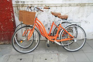 orange bicycle park near wall