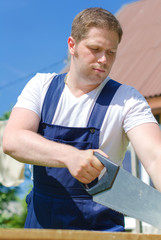 Handsome handyman sawing long wooden plank outdoors