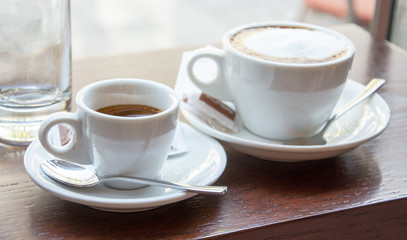 Espresso and cappuccino cups standing on the wooden table