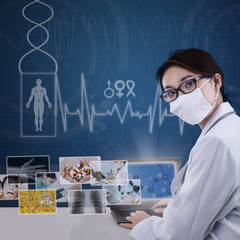 Attractive modern doctor working on laptop