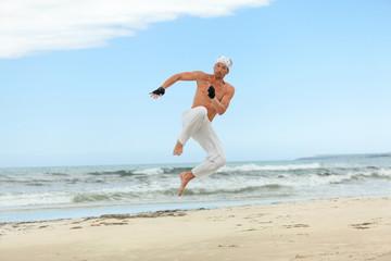 erwachsener sportlicher mann am strand springt karate