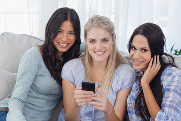 Smiling friends holding smartphone looking at camera