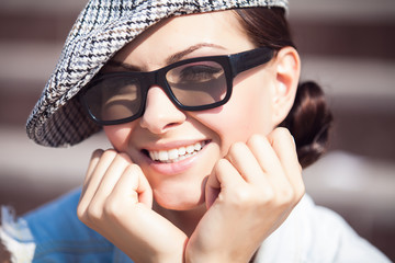 Close-up portrait of beautiful smiling girl with hat and glasses