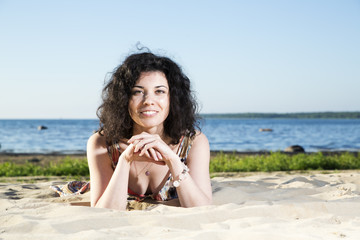 Happy woman with hairs lying at beach