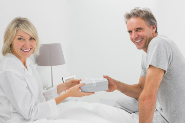 Man giving present to his smiling partner looking at camera
