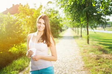 Beautiful young woman holding coffee cup hiking in the park