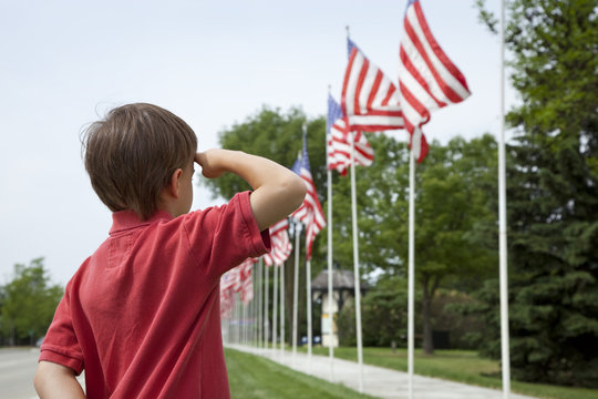 Boy salutes flags at Memorial Day display in a small town