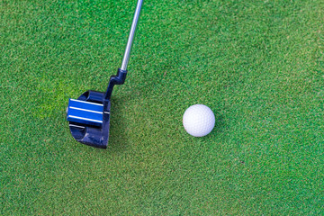 Golf stick and ball near the hole.