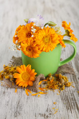 Calendula flowers in cup on wooden background