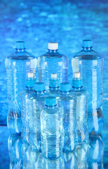 Water in different bottles on blue background