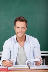 lächelnder mann mit aktenorder vor einer tafel