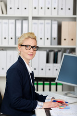 junge frau mit brille arbeitet am computer