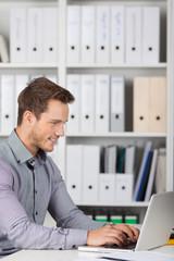 lächelnder mann arbeitet am laptop