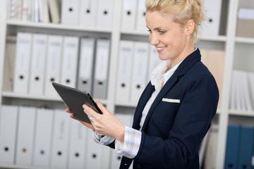 lachende blonde frau mit tablet im büro