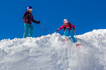 Girl skier with his mother on a steep slope in the mountains