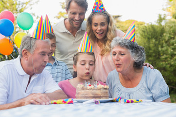 Happy extended family watching girl blowing out birthday candles