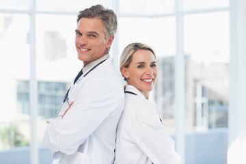 Smiling doctors posing together back to back