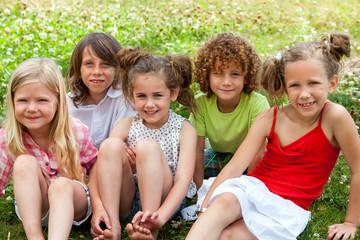 Children sitting together in flower field.