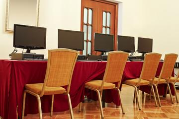 Desktop computers on table in auditorium