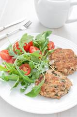 Fish patties with parsley and arugula tomato salad