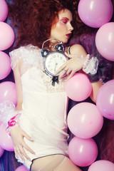 woman lying on floor among balloons