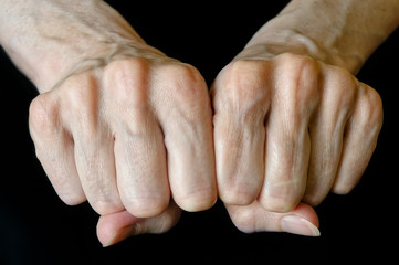 Senior woman showing fists on black background