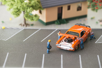 Miniature mechanics working on a car close-up