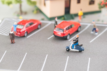 Busy street with miniature people, cars and scooter close-up