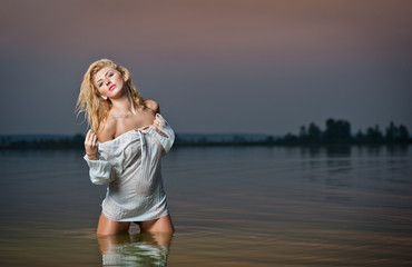 Beautiful young woman in a white wet blouse in the river