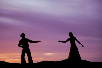 Cowboy reach for woman silhouette