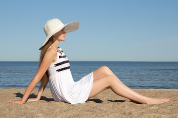 pretty woman in striped dress and hat sitting on the beach