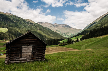 A view of typical alpine valley with rustic hut.