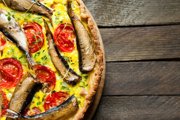 quiche with a fish on the wooden table