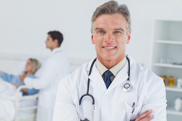 Experienced doctor posing with doctor attending patient on backg