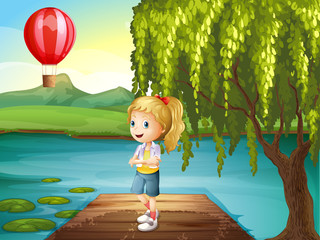A girl standing above the wooden bridge with a hot air balloon n