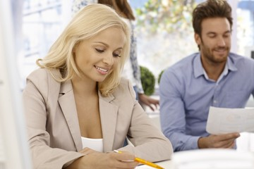 Attractive businesswoman writing notes