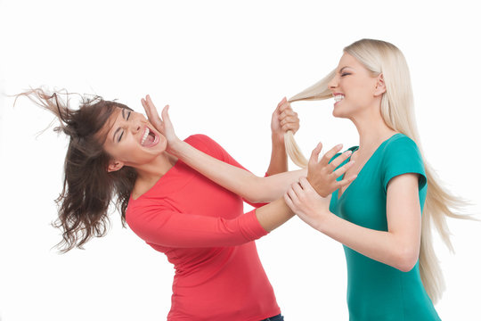 Women fighting. Two furious women fighting while standing isolat