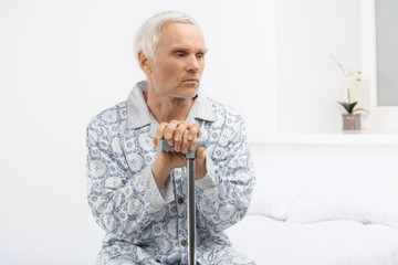 Loneliness. Depressed senior man leaning at his cane while sitti