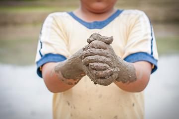 Boy hands with mud