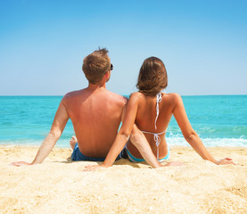 Wall Mural - Young Couple Sitting together on the Beach. Vacation concept