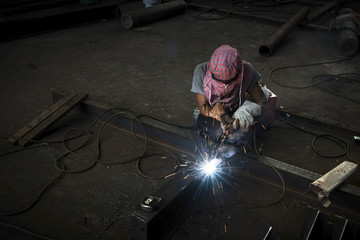 Skilled welder at work with sparks arcing.