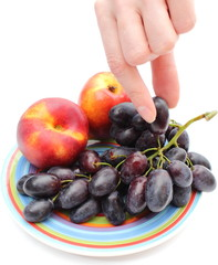 Hand and fruits on colorful plate